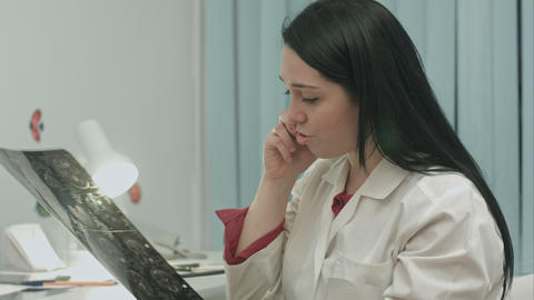 Beautiful female doctor talking on cellphone at modern hospital indoors Footage