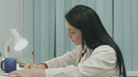 Tired female doctor sits in a medical office in the clinic and writes diagnose o Footage