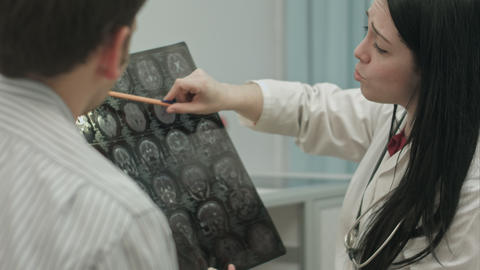 Female doctor in clinic show x-rays to male patient Footage