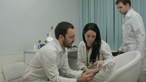 Two physicians in good mood analyze results of patient to diagnose disease, then Footage