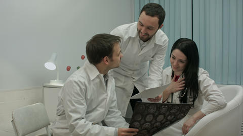 Two physicians checking patient's head scanning, then comes physician with good  Footage
