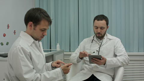 Two male doctors at medical cabinet using mobile phones Footage