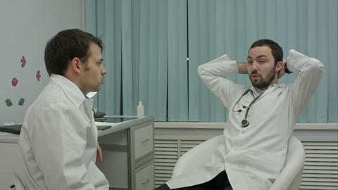 Two doctors relaxing at modern hospital indoors, speaking about life and work Footage