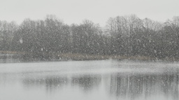 Dense snowfall in front of a lake Footage