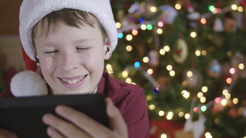 Front View of Young Boy Wearing Santa Hat and Headphones Laughing at Video on Ta Footage