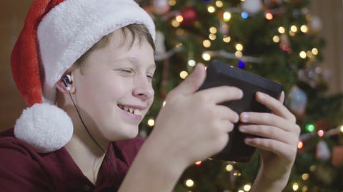 Side View of Young Boy Wearing Santa Hat and Headphones Laughing at Video on Tab Live Action