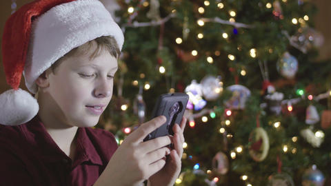 Young Boy Wearing Santa Hat Playing Game App on Cell Phone by Christmas Tree Footage