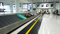 Baggage carousel at arrival airport hall, moving suitcases on transporter tape Live Action