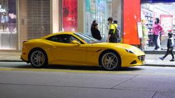 Luxury Ferrari California car parked on the night street of Hong Kong Footage