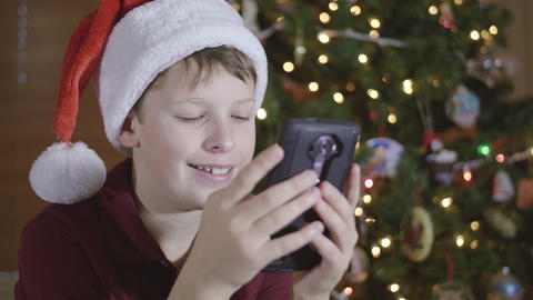 Young Boy Wearing Santa Hat Reacting and Responding to Text Message on Cell Phon Footage
