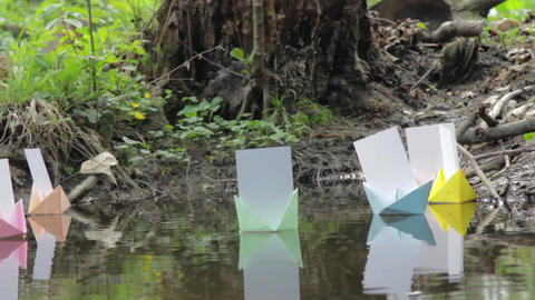Colored paper boats float on the water of ponds in the dark forest 138 Footage