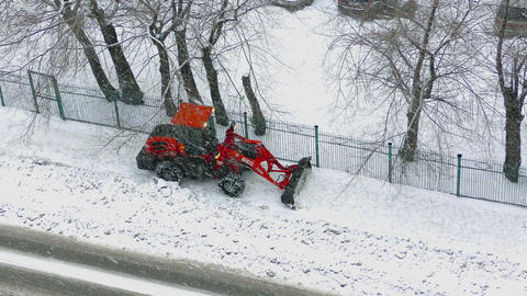 Bright red tractor clears the sidewalk Footage