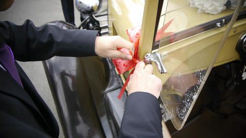 Male bind a ribbon by mirror of a vintage car 58 Footage