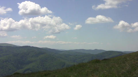 Horizontal panorama with forested mountains and white clouds floating above them Footage