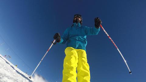 Alpine skier skiing slalom, camera on ski, blue sky on background Footage