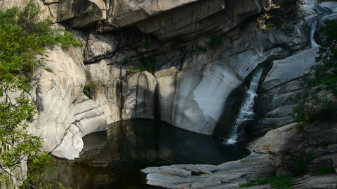 Mountain waterfall stream into pool from multilayer stone,forests & shrubs Footage