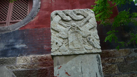 Stone monument with dragon pattern at temple entrance,shaking tree shadows Footage