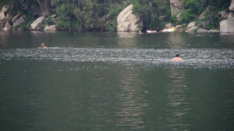 People swimming in lake,relying on Castle Peak Stock Video Footage