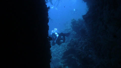 Divers swim through the underwater tunnel, Red Sea Stock Video Footage