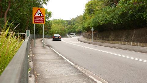 Traffic on dangerous mountain road, warning sign Footage