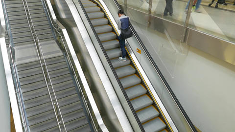 Empty staircase parallel with escalator, travelling up, people on the escalator Footage