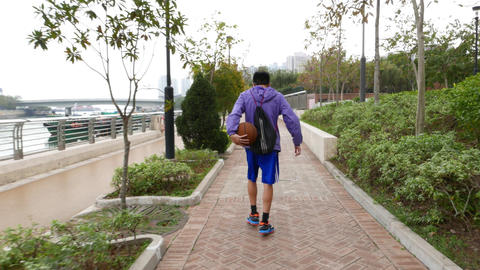Young boy walking and play basketball tricks, throwing ball, spinning Footage