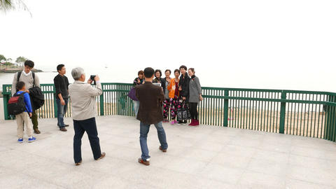 Family and friends take picture together against seascape Footage