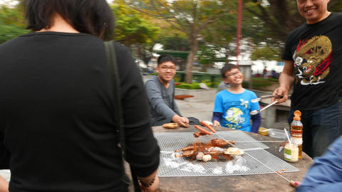 Happy faces around picnic table, smiling children roast sausages Footage