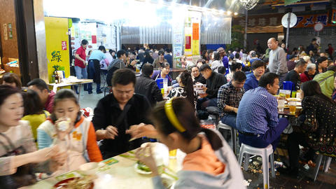 Extremely crowded street eatery area, road restaurants in night time Footage