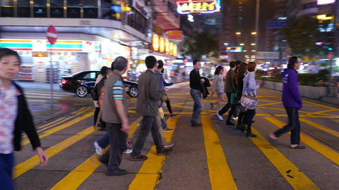 Pedestrians crowd crossing night street in dynamic tracking shot Footage