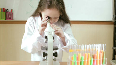 Child scientist looking into microscope MCU slider in Footage