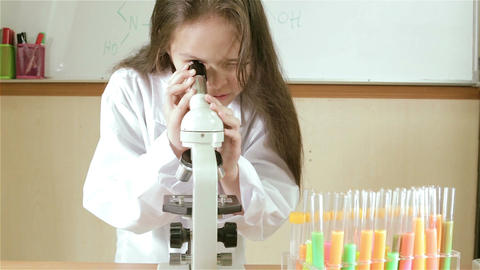 Child scientist looking into microscope MCU slider out Footage