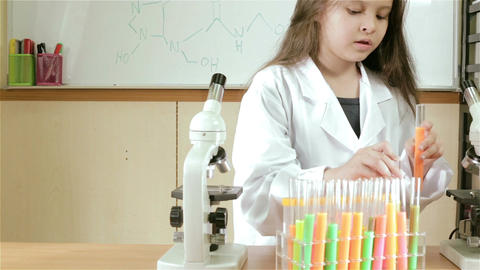 Child scientist putting test tubes away and checking microscope slider Footage