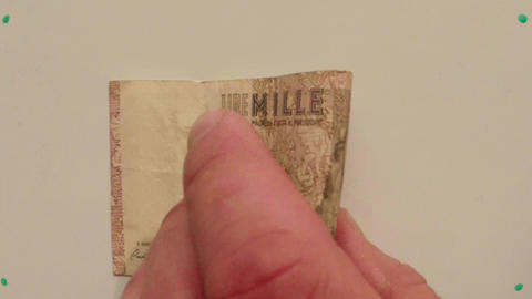 paper money 1000 Italian lire on white table flipped a hand close up Footage