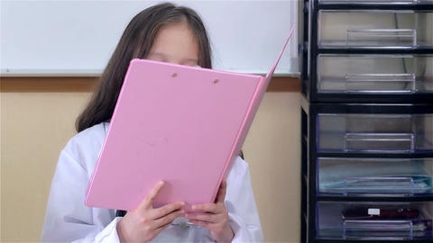 Young child doctor checking file and smiling at camera Footage
