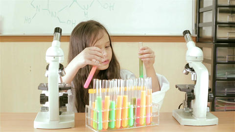 Young girl scientist inspecting test tube reaction Footage