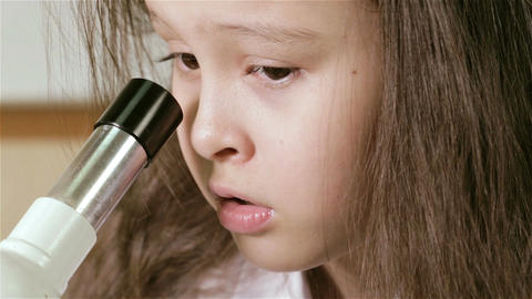 Young girl scientist looking into microscope and around d Footage