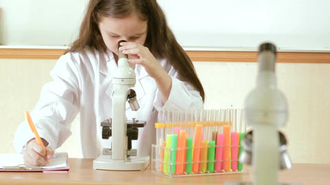 Young girl scientist looking through microscope and making notes Footage