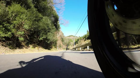 Rear wheel view. Rider is running on a narrow mountain road Footage