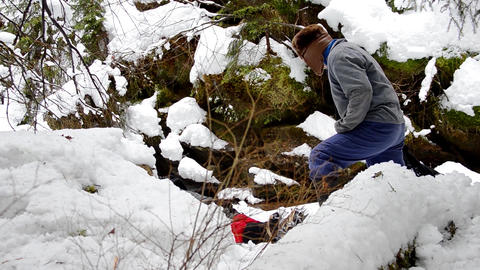 Forestry worker who looks at a body lying on snow near a mountain river 24 Footage