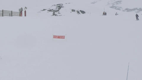 Skiers descend on a landscaped slope while snowing outside and snow is deposited Footage