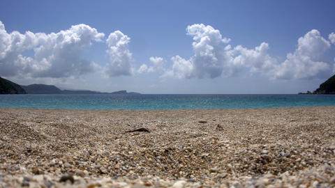 Rocky sand and clear blue sea water and fluffy clouds that reflect the blue sky  Footage