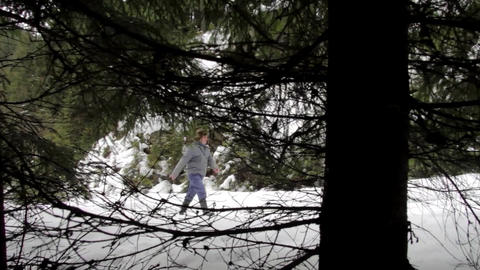 Speed forestry worker who goes on a road covered with snow in the woods seen beh Footage