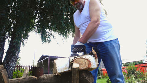 Elderly man in protective glasses sawing birch log Footage