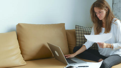 Woman using laptop and working with documents Footage