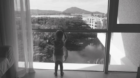 Little girl standing near big wide window and welcomes airplane which going to l ビデオ