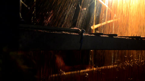 Mid close shot of an Indian weaver weaving in dramatic light