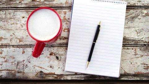 Coffee cup, notepad, pen on wooden plank Footage