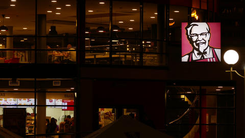 4K Ungraded: Windows of Two-Storey KFC Restaurant With Customers Glow in The Footage