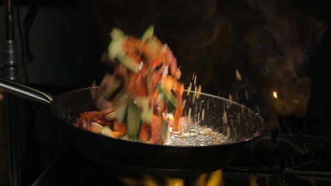 Person Shakes Cut Vegetables on Pan above Open Flame Footage